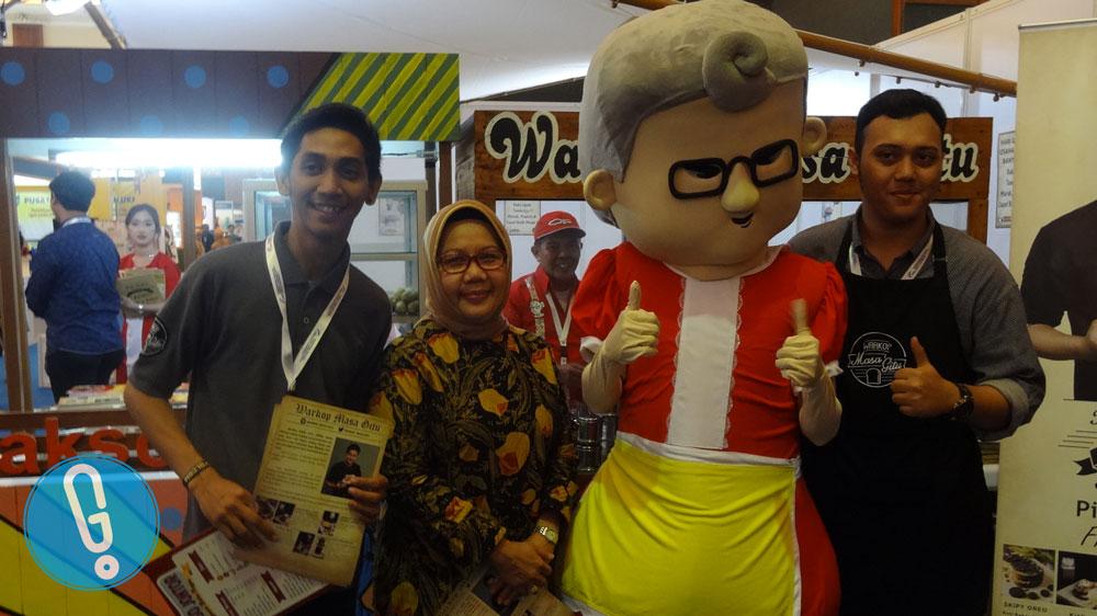 Ibu Srie Agustina berfoto besama salah satu booth waralaba asal Indonesia di IFRA 2016 (foto: Genmuda.com/2016 Liki)