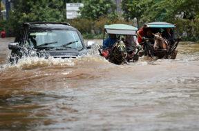 Sebuah mobil berusaha menerobos genangan banjir di kawasan Kelapa Gading, Jakarta Utara, Selasa (10/2).